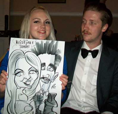 Daniel and kristina loves how there hair is caricatured in the picture at a event in brighton