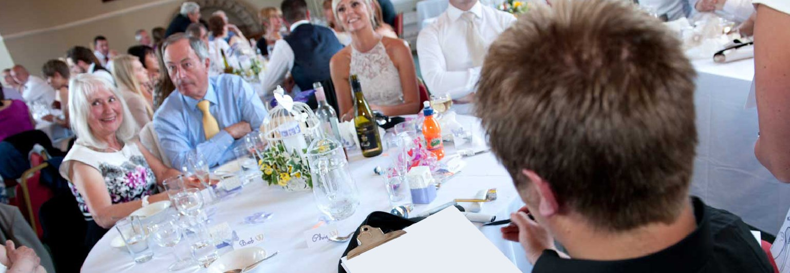 Caricaturist drawing around the tables in central London wedding