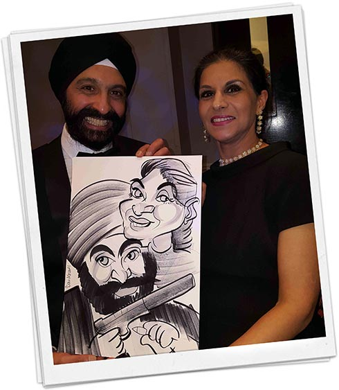 Sikh man and his wife holding their caricature