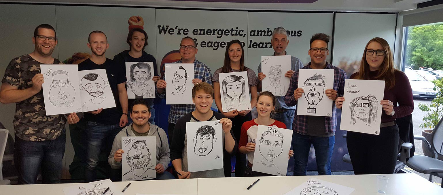 this photo shows the team drawing themselves after a Caricature Workshop from David Groves