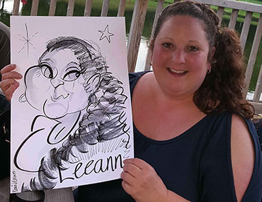 Leeann sitting with her caricature at a corporate function