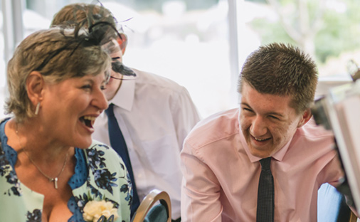Mother and son laughing at there caricature at a Kent Wedding