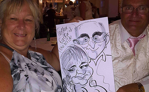 Wedding Caricaturist get the parents of the Bride to pose with their caricature