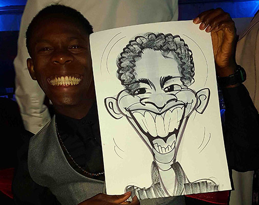 Big smile and all teeth as the subject poses with his caricature
