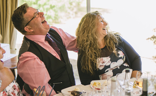couple laughing at the there caricature at the Wedding breakfast