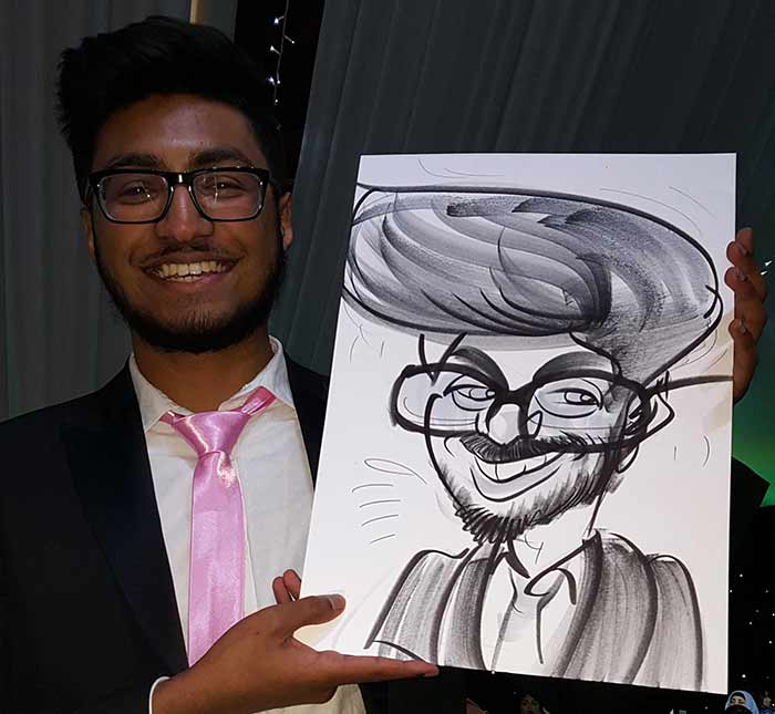 asian wizard holds his caricature up and smiles