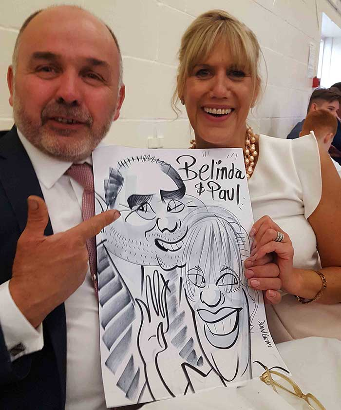 Paul and Belinda show off their caricature
