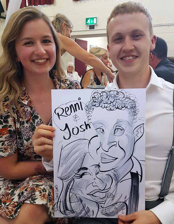 Renni and Josh smile holding their caricature