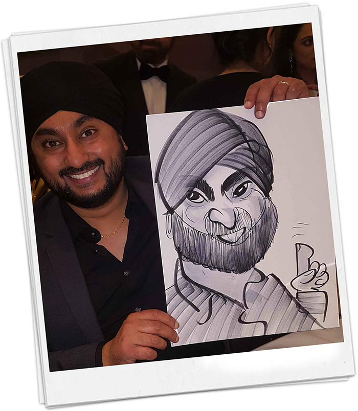 Man with Turban posing with a caricature at a Asian Wedding
