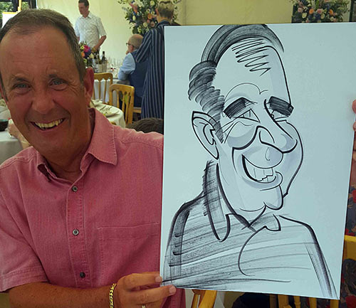 guys holds his caricature at summer garden party