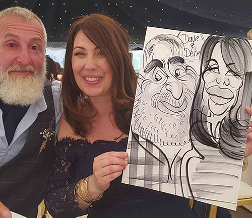Dave and Debs hold their caricature