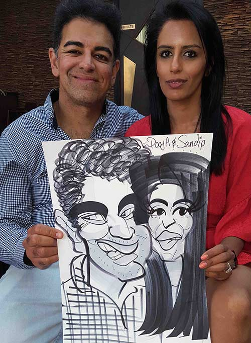 pooja and sandip holding their caricature