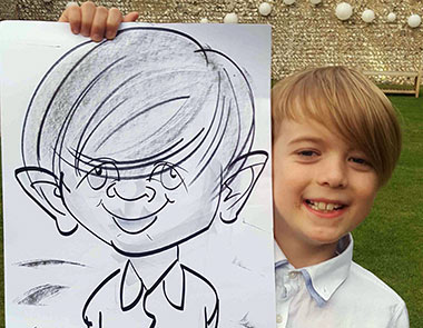 Child holding his caricature at Cissbury Barn