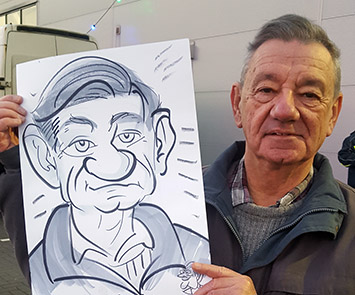 man with a big hooter holds his caricature up