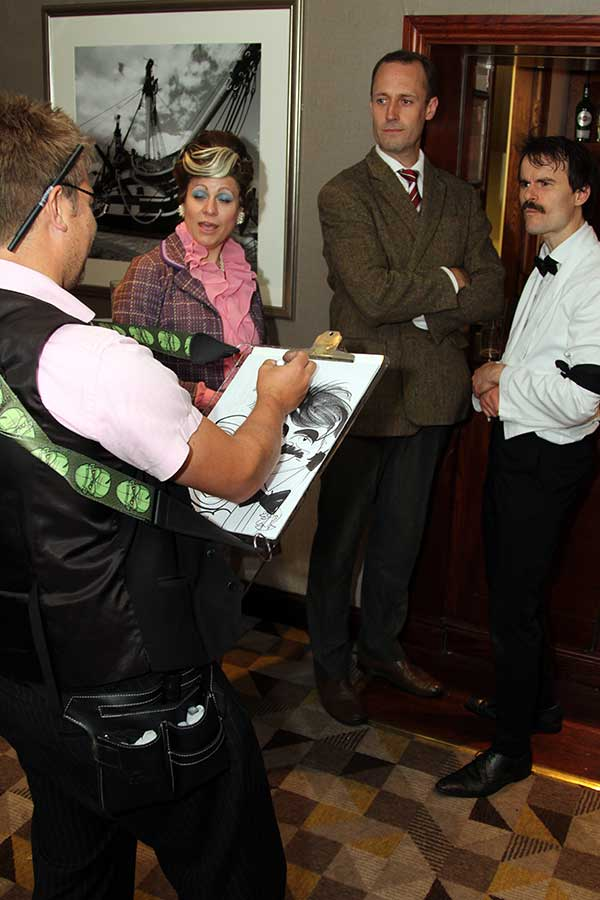 Caricaturist drawing Faulty Towers actors at a Faulty Towers Dinner Night